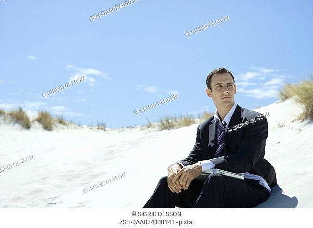 Businessman sitting on sand dune, closed laptop on lap