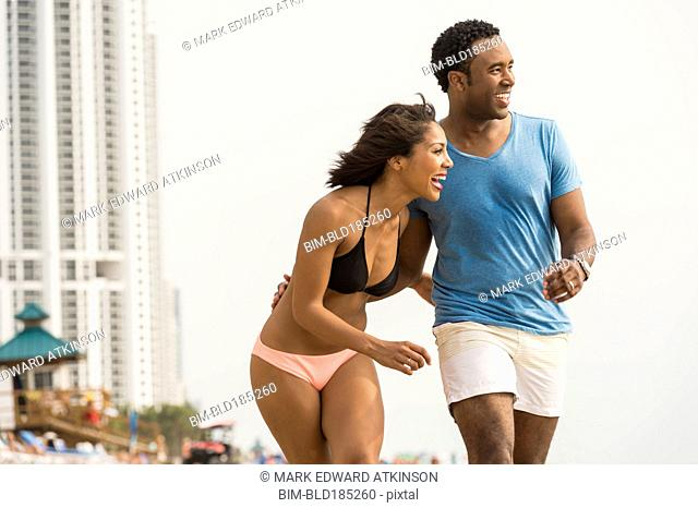 Couple laughing and walking on beach