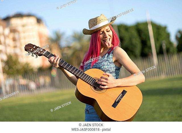 Young woman with hat playing guitar