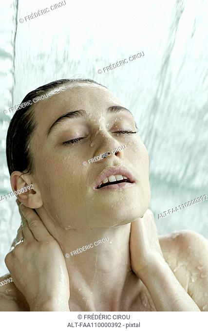 Woman bathing in artificial waterfall