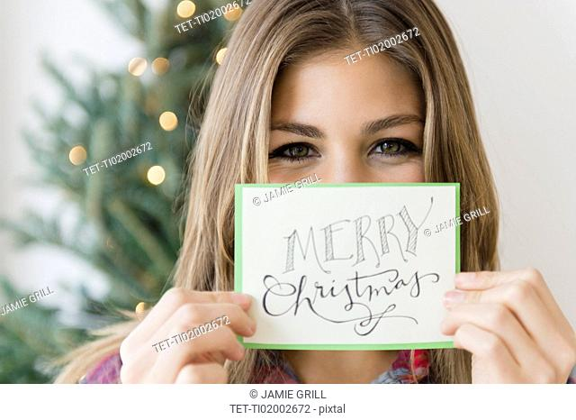 Young woman holding greeting card for christmas