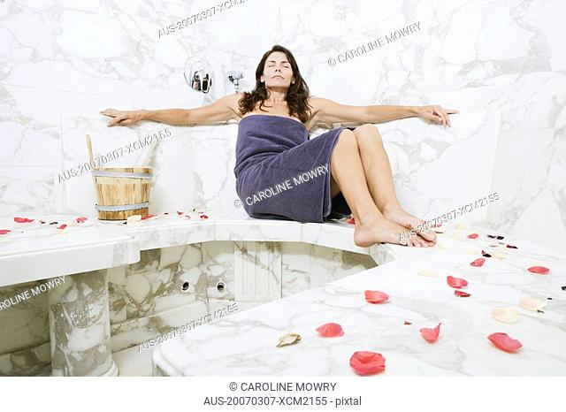 Mid adult woman sitting in the bathroom