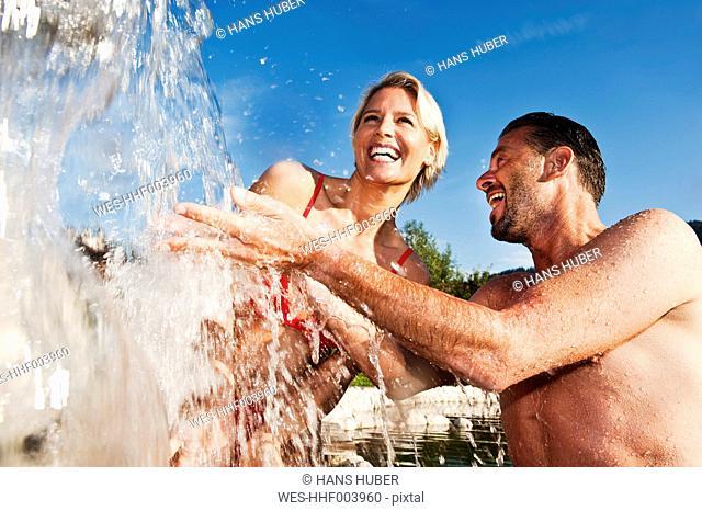 Austria, Salzburg County, Couple standing under waterfall