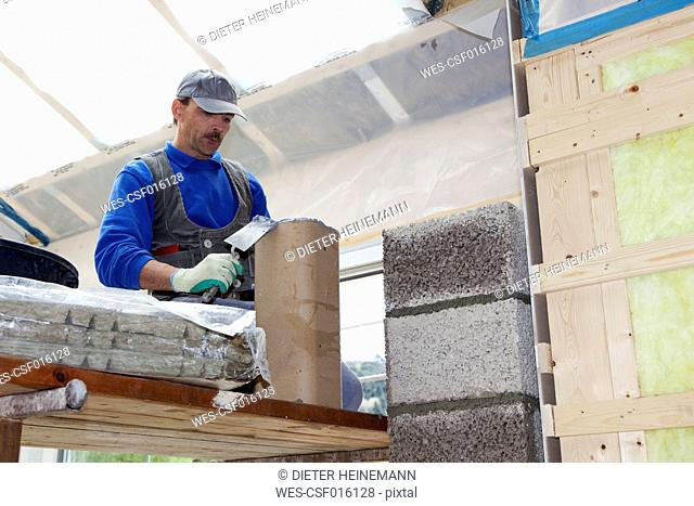 Europe, Germany, Rhineland Palatinate, Worker installing thermal insulation