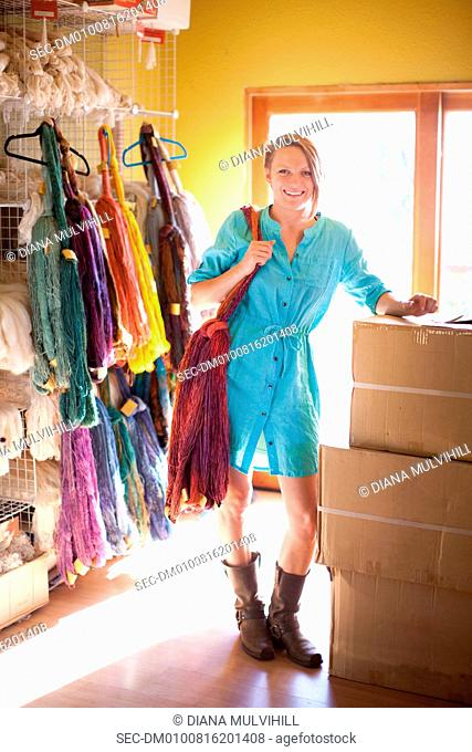 Woman standing next to hanging yarn