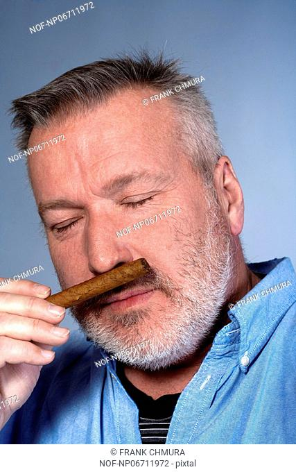 studio portrait of a middle aged man in shirt with a cigar