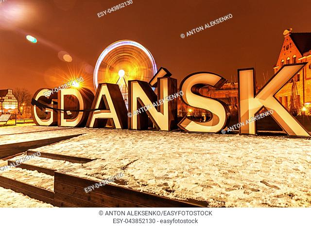Gdansk city sign and the ferris wheel near Motlawa river, night winter view