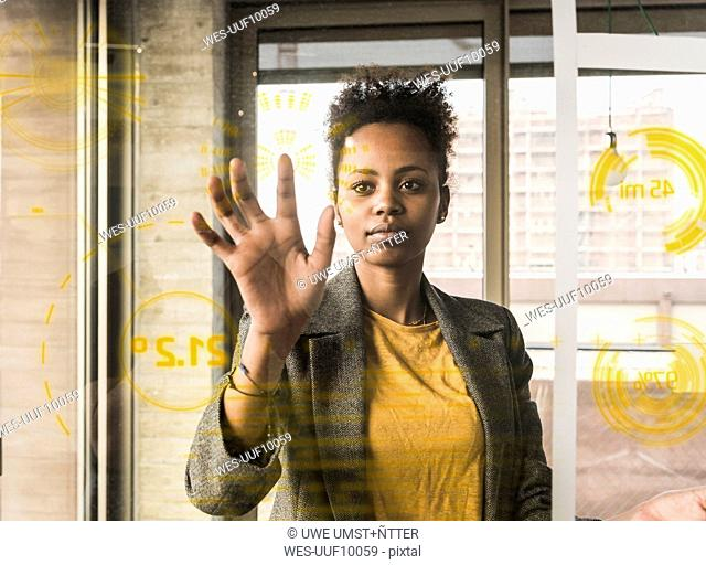 Young woman touching glass wall with data in office
