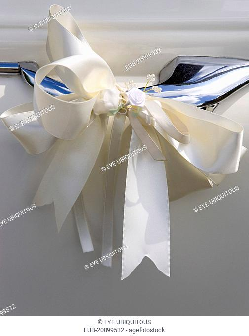 Cream ribbon tied in bow on door handle of vintage white Daimler wedding car
