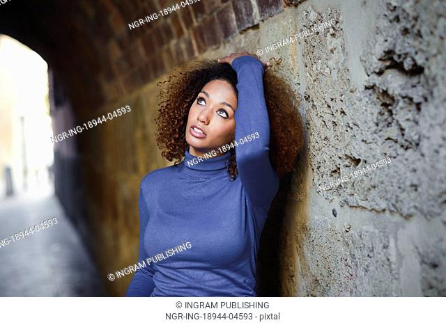 Beautiful young African American woman, model of fashion, with afro hairstyle and green eyes wearing blue sweater in urban background
