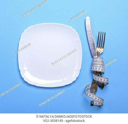 knife with a fork wrapped in a measuring tape with a white square ceramic plate, top view, blue background