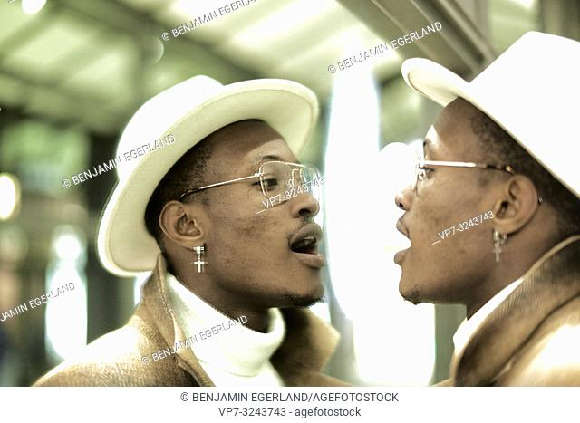 man breathing on mirror, looking at himself, self-perception, wearing Christian cross earring, in Munich, Germany