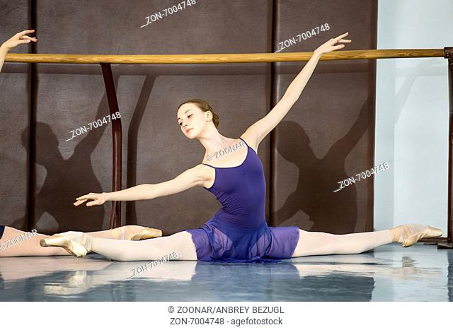 Young ballerinas on the lesson of classical choreography sitting in the splits gracefully raising his hands up near barre
