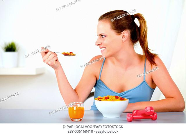 Portrait of a caucasian young woman smiling and eating healthy meal at home indoor