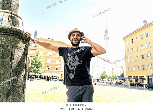 Germany, Berlin, smiling man on the phone with television tower in the background