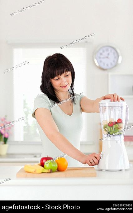 Cute brunette female using a mixer while standing