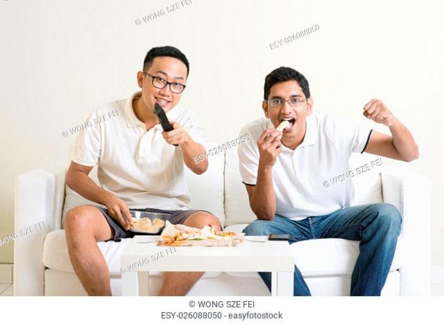 Friendship, technology and home concept. Smiling male friends with remote control and junk food at home