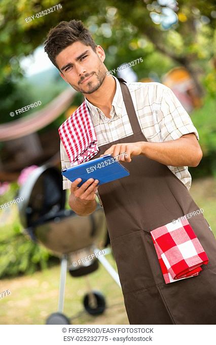 Chef looking for a recipe on tablet for a barbecue, France