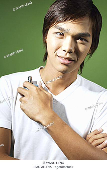 Young man looking at camera, holding bottle of perfume