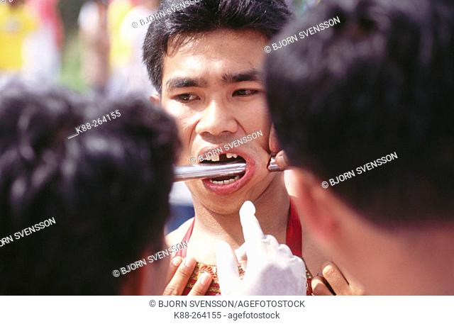Medium in trance gets pierced by priest. Vegetarian Festival in Phuket. South Tahiland