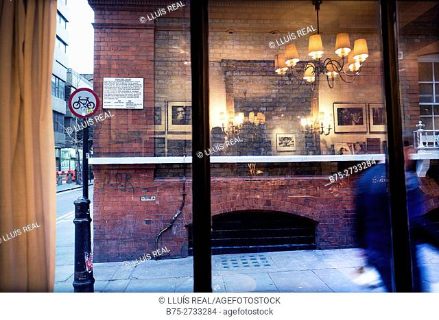 Looking at street view through window. Lamp, furniture and photographs reflected in glass. Silver Pl. , Soho, London, England
