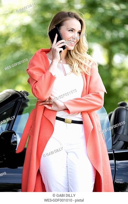 Portrait of smiling blond woman telephoning with smartphone in front of black sports car