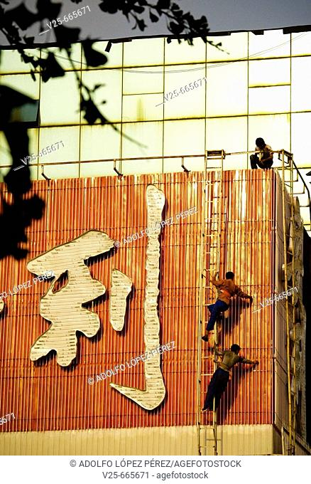 Workers repairing sign. China