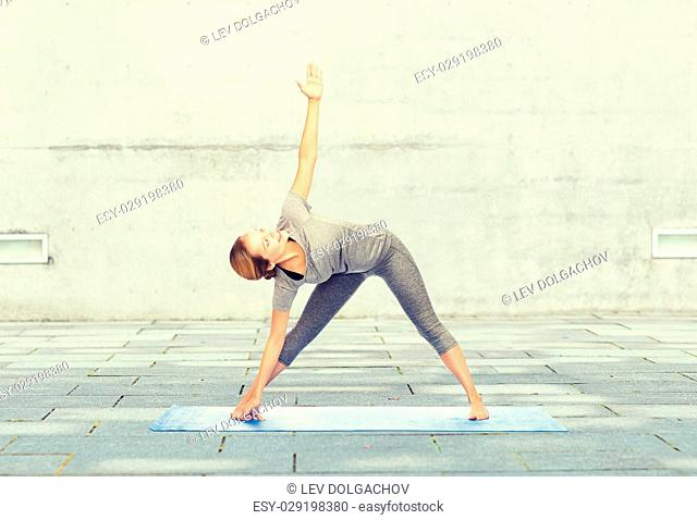 fitness, sport, people and healthy lifestyle concept - woman making yoga triangle pose on mat over urban street background