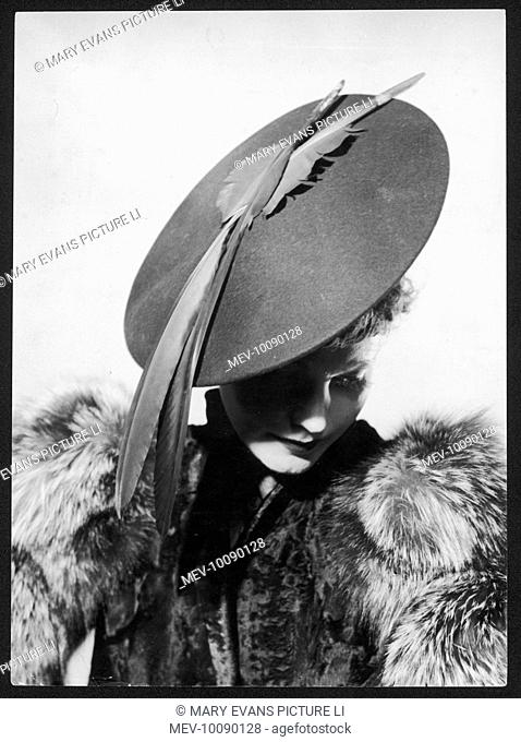 A large, flat, felt hat worn at an acute angle, with two big feathers attached to the top. The model is also wearing a fur coat
