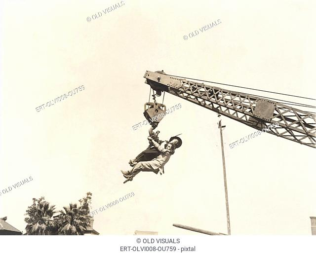 Two people dangling from crane