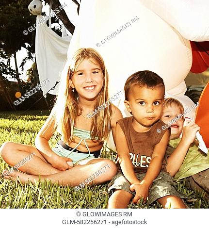 Portrait of three children sitting in the lawn and smiling