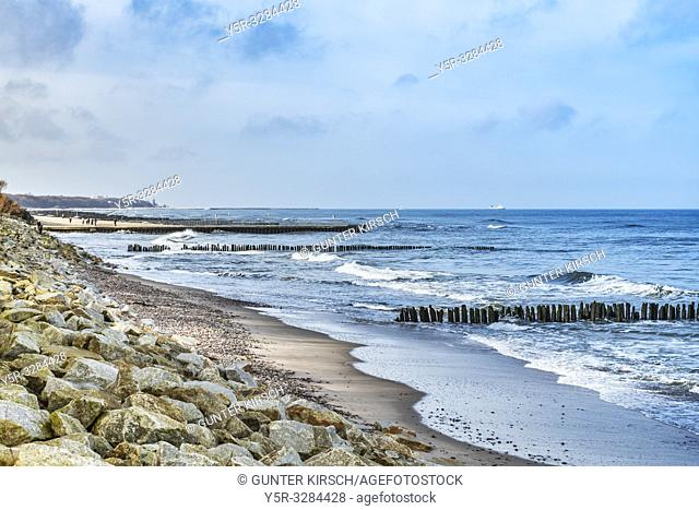 Beach with stones and old groynes on the Baltic Sea. Groynes are intended to break the shaft and to prevent the erosion of the coast