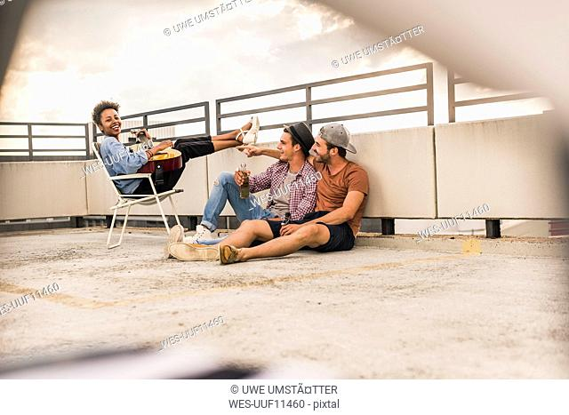 Three friends having a rooftop party