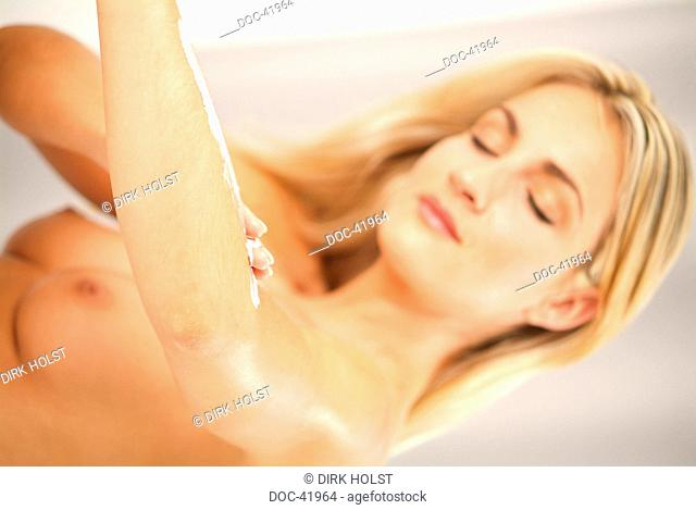 young woman is using cream on her arm