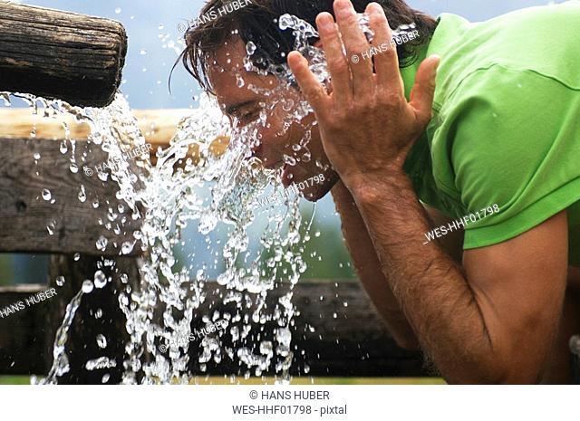 Brunette man drinking water, portrait