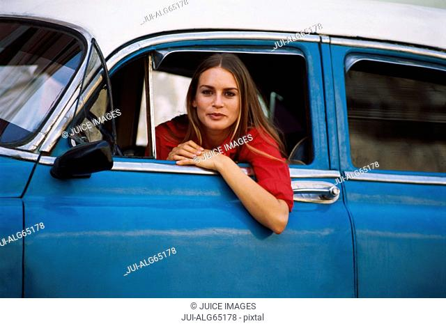 Woman sitting in the driver's seat of a blue car, Cuba