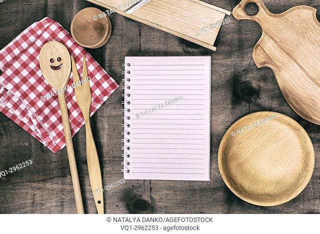 open notepad with wooden kitchen objects on a brown background, top view