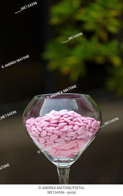 Pink color wedding confetti, sugar almonds in a transparent bowl