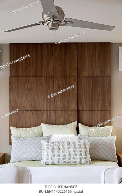 Fan over tidy bed with large wooden headboard in bedroom at home