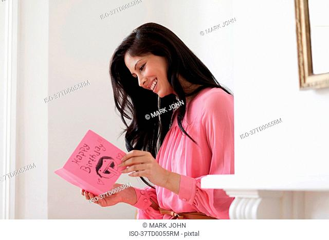Smiling woman reading birthday card