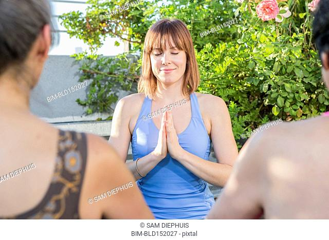 Teacher working with yoga students outdoors