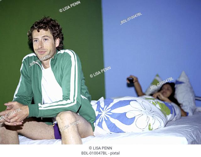 man sitting on bed semidressed looking sceptical, woman in background with remote control