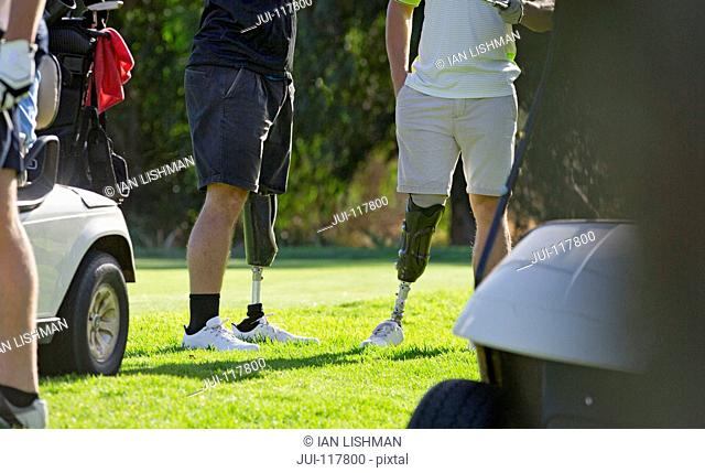 Close Up Of Male Golfers With Artificial Legs Standing By Green