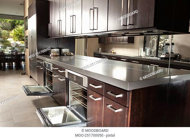 Dark wood kitchen island with open oven doors