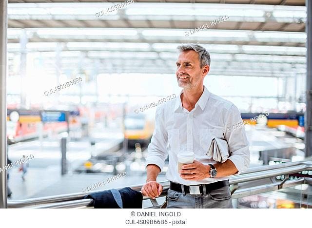 Mature man at train station, holding takeaway coffee cup