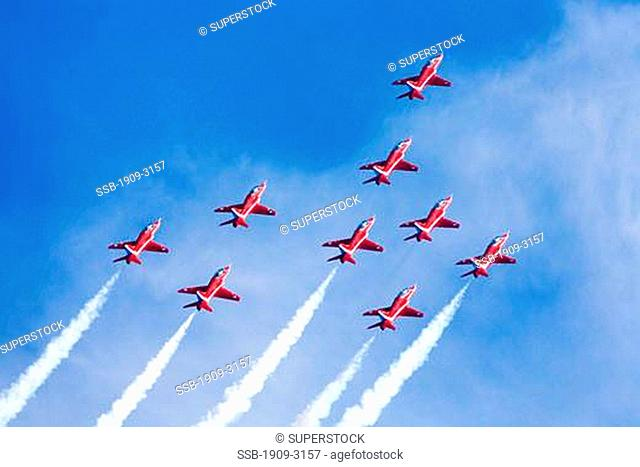 Red Arrows Royal Air Force RAF aerobatic display team in Hawk trainer aircraft at Fairford international air tattoo 2006 display smoke vapour trails in the...