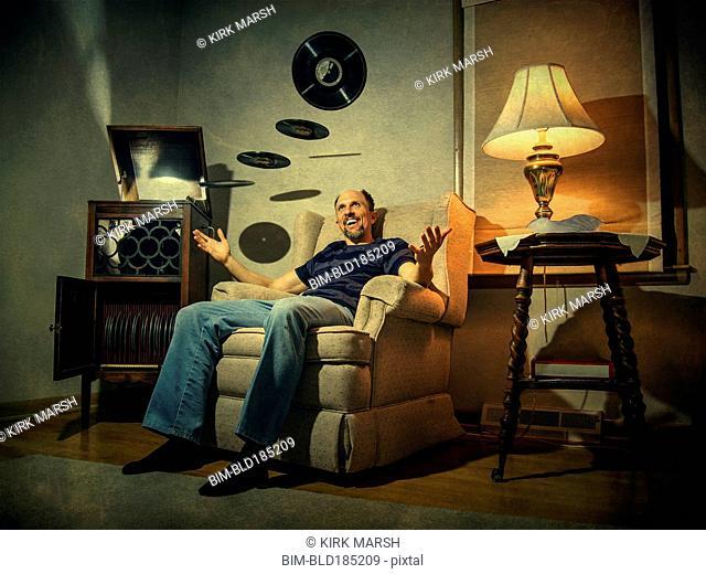 Caucasian man levitating records in living room