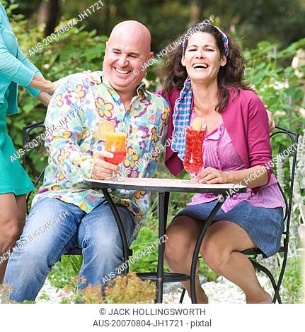 Mature couple sitting at a table holding glasses of juice and smiling