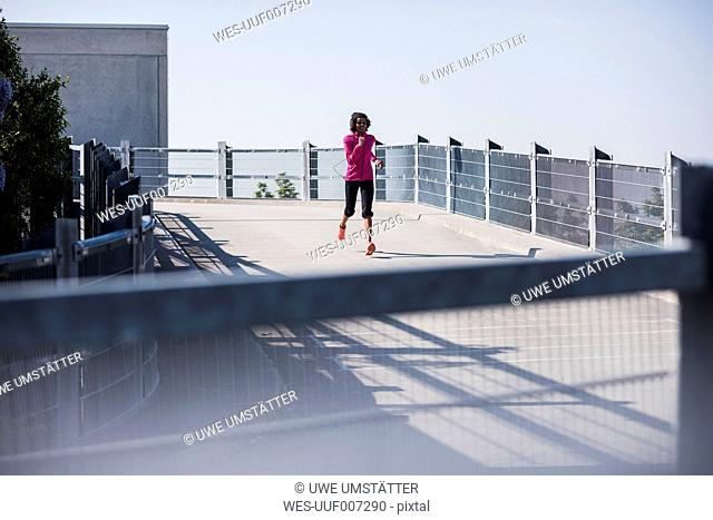 Young woman running on parking deck