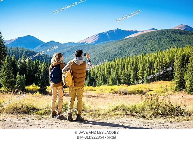 Hispanic couple photographing mountains, Breckenridge, Colorado, United States